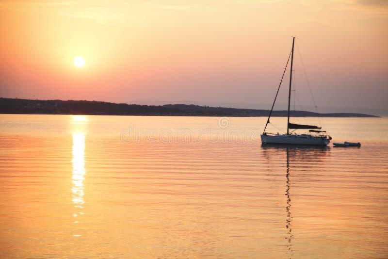 O barco de navigação flutua no mar calmo no nascer do sol imagem de stock