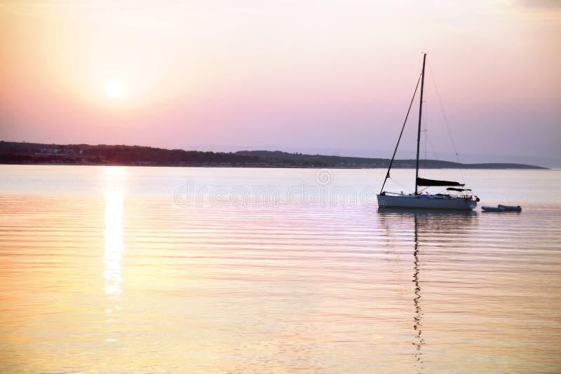O barco de navigação flutua no mar calmo no nascer do sol imagens de stock royalty free