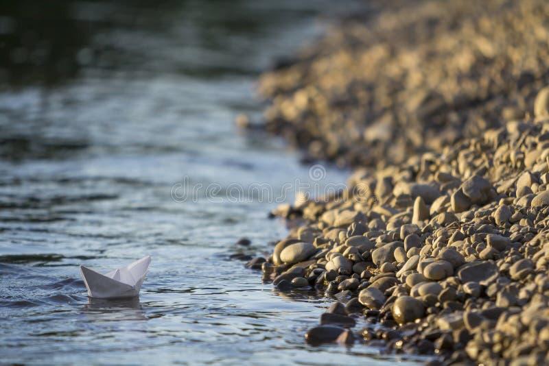 O barco de papel do brinquedo do origâmi branco pequeno simples que flutuam no rio claro ou a água do mar na água azul borrada e  imagens de stock royalty free