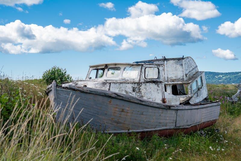 O barco de pesca abandonado senta-se em um pântano em Homer Spit em Alaska Dia ensolarado fotos de stock