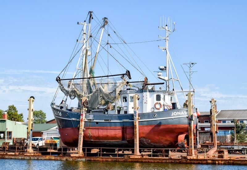 O barco de pesca com o nome JONAS SU 16 está sendo reparado em um estaleiro em Buesum no Mar do Norte em Alemanha imagem de stock royalty free