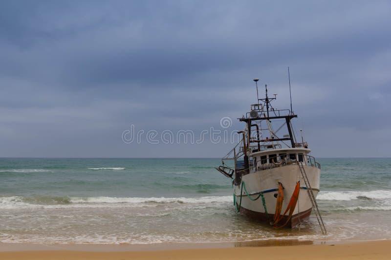 O barco de pesca corre encalhado na praia fotos de stock