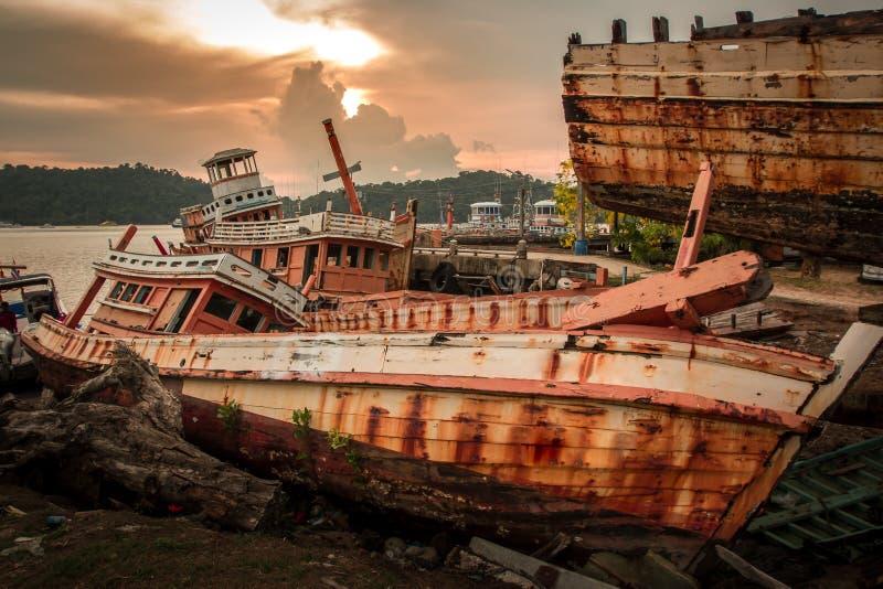 O barco de pesca quebrado saiu abandonado na terra perto do porto fotos de stock royalty free