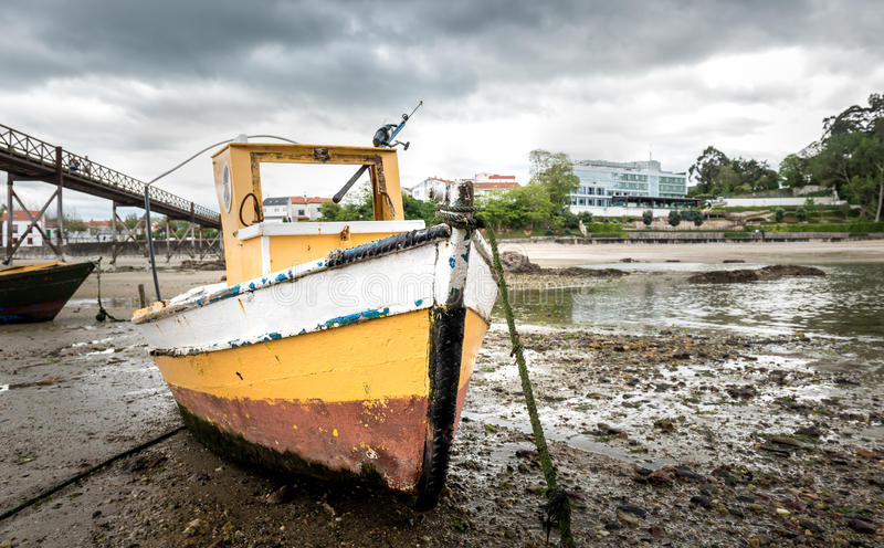 O barco de pesca velho é amarrado na praia na maré baixa fotografia de stock