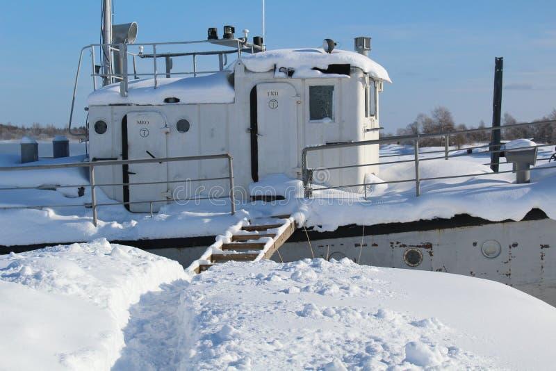 O barco de rio está em um cais coberto de neve no inverno fotografia de stock royalty free