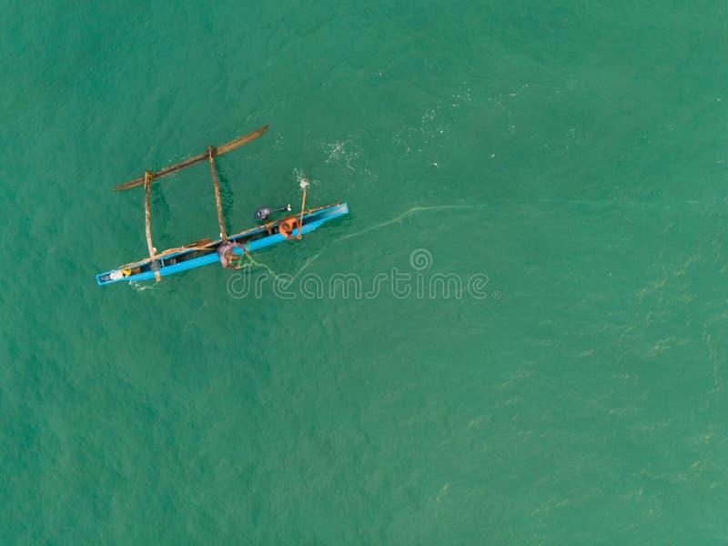 O barco de Sri Lanka dos pescadores joga a rede na água fotografia de stock
