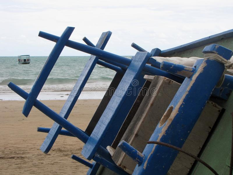 O barco inclinado empoleirou-se na areia com fundo do mar foto de stock royalty free