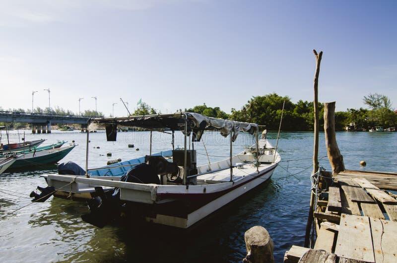 O barco malaio tradicional do pescador amarrou, molhe de madeira e bl imagem de stock