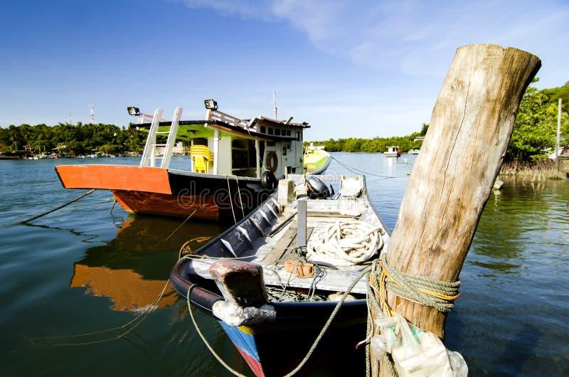 O barco malaio tradicional do pescador amarrou perto do riverbank, imagem de stock