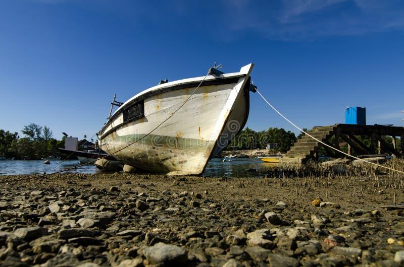 O barco malaio tradicional do pescador amarrou perto do riverbank o fotos de stock royalty free