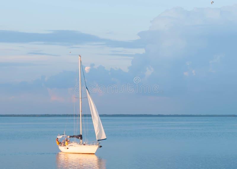 O barco navega e molda a reflexão de incandescência alaranjada no céu azul e cor-de-rosa imagens de stock royalty free