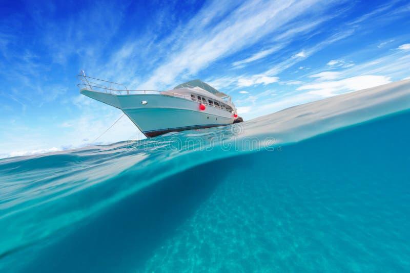 O barco pequeno do safari com separação bonita disparou sob e acima do wate fotos de stock royalty free