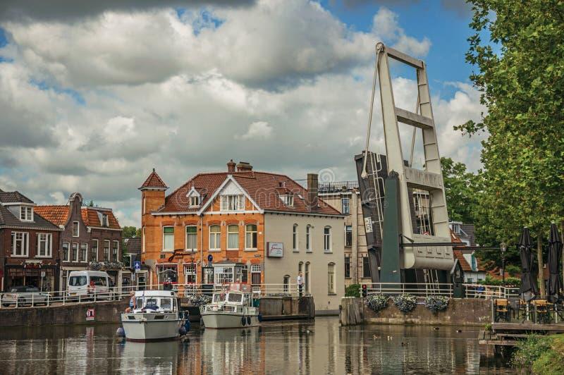 O barco que passa pela ponte de bascule aumentou no canal largo árvore-alinhado no dia nebuloso em Weesp fotografia de stock royalty free