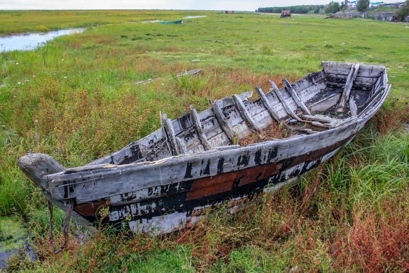 O barco velho destruído no tempo encontra-se perto da água no campo imagens de stock