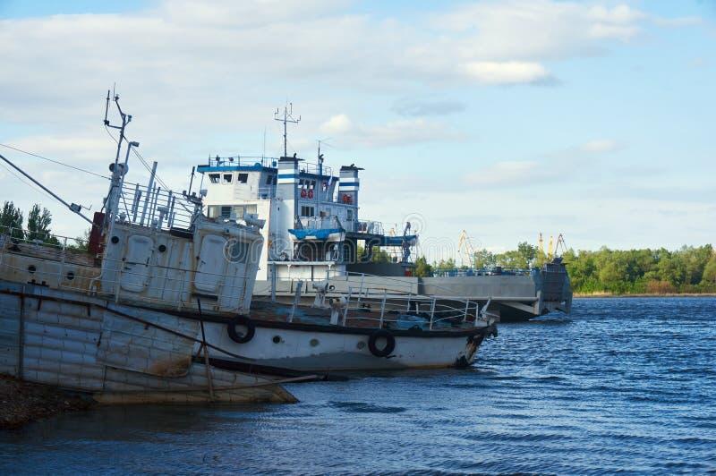 O barco velho e a balsa na costa no rio em um dia de verão ensolarado foto de stock
