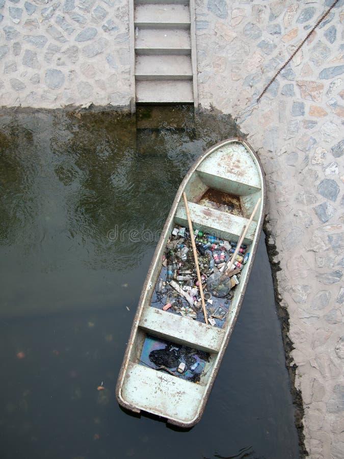 O barco velho para recolher o desperdício doméstico que flutua na água vale perto da margem foto de stock