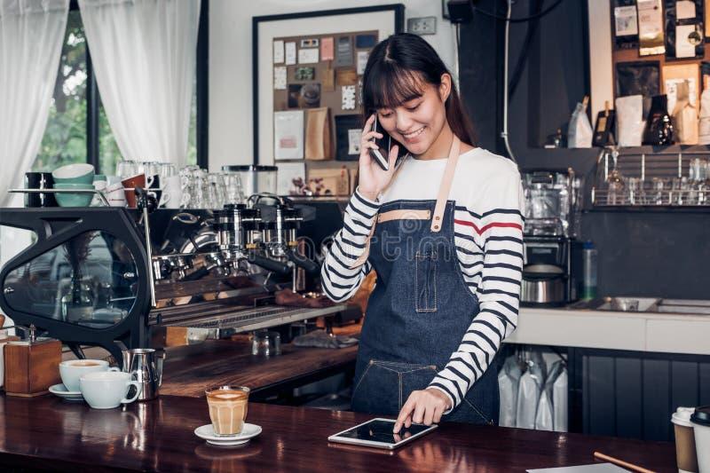 O barista da mulher toma a ordem pelo móbil e pela tabuleta, waitre da fêmea de Ásia imagem de stock royalty free