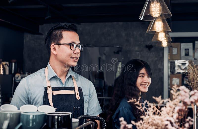 O barista masculino e fêmea que fala com cliente provou aproximadamente do co fotos de stock