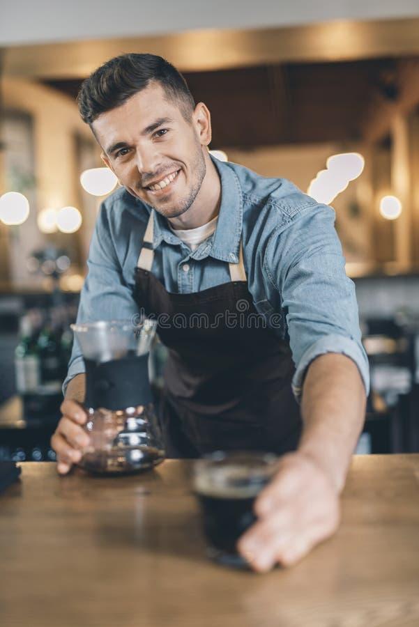 O barista novo amigável que sorri à câmera e que dá derrama sobre imagem de stock royalty free