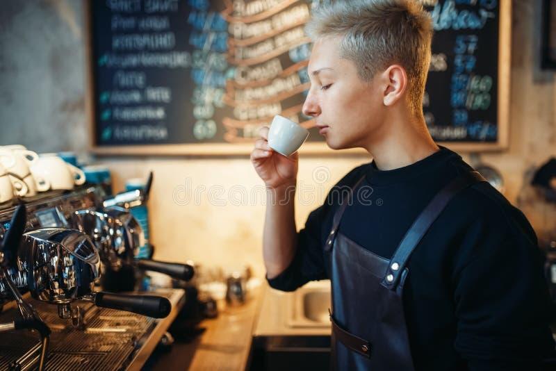 O barista novo prova o café preparado fresco no café imagem de stock royalty free