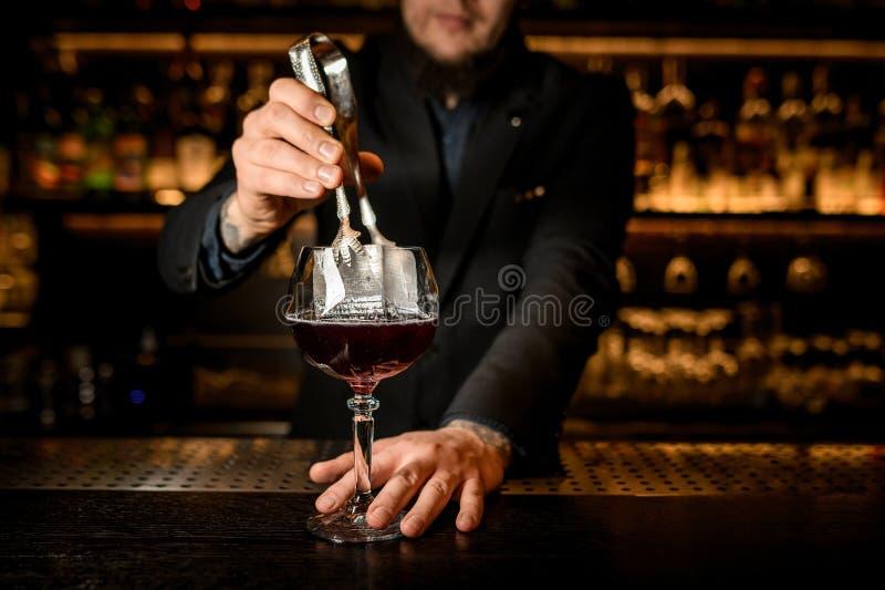 O barman adiciona o cubo de gelo grande em um cocktail foto de stock