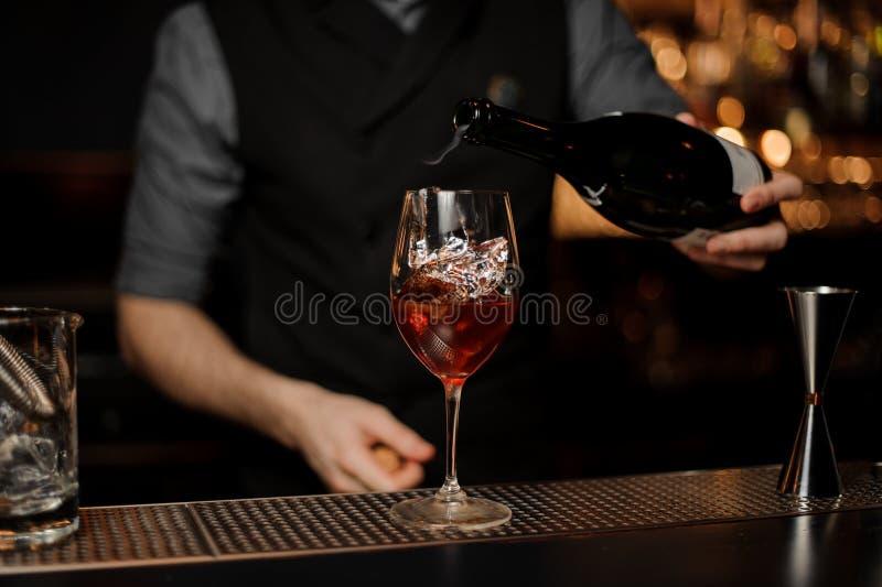 O barman adiciona o vinho espumante no cocktail em um contador da barra fotos de stock