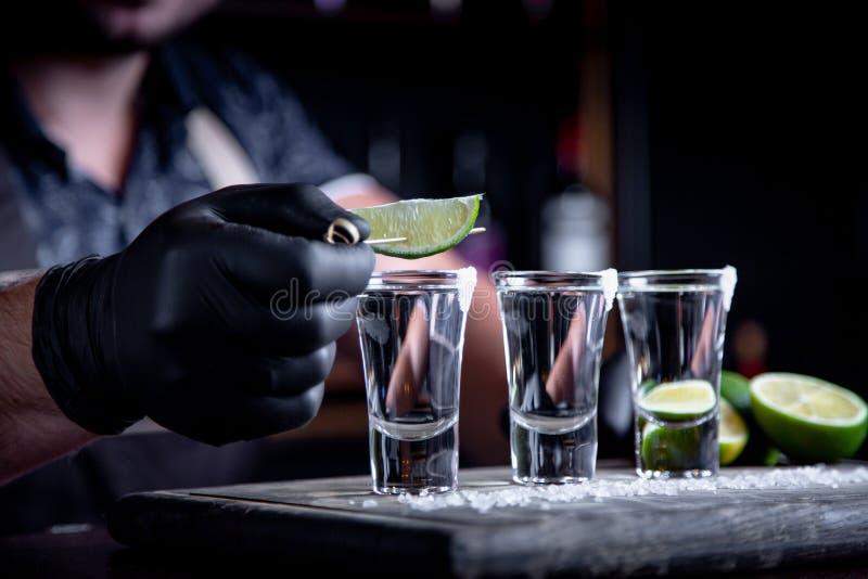 O barman decora dentro tiros do cal do tequila Mexicano, álcool em vidros disparados fotos de stock