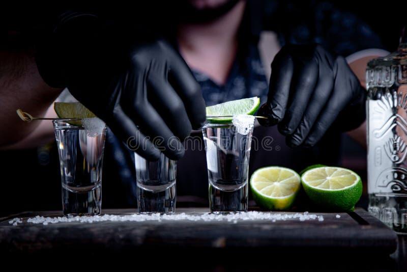 O barman decora dentro tiros do cal do tequila Mexicano, álcool em vidros disparados fotografia de stock