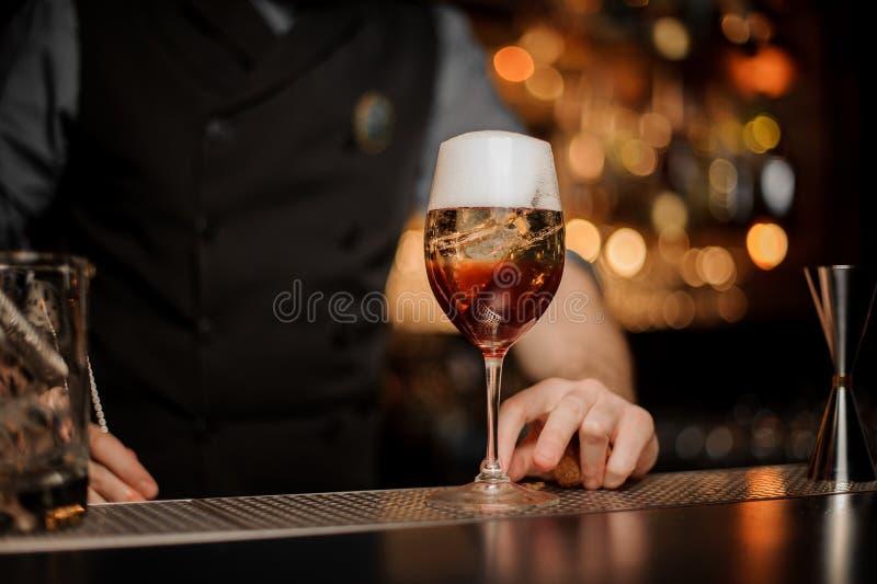 O barman derrama o cocktail com aperol e vinho espumante fotos de stock