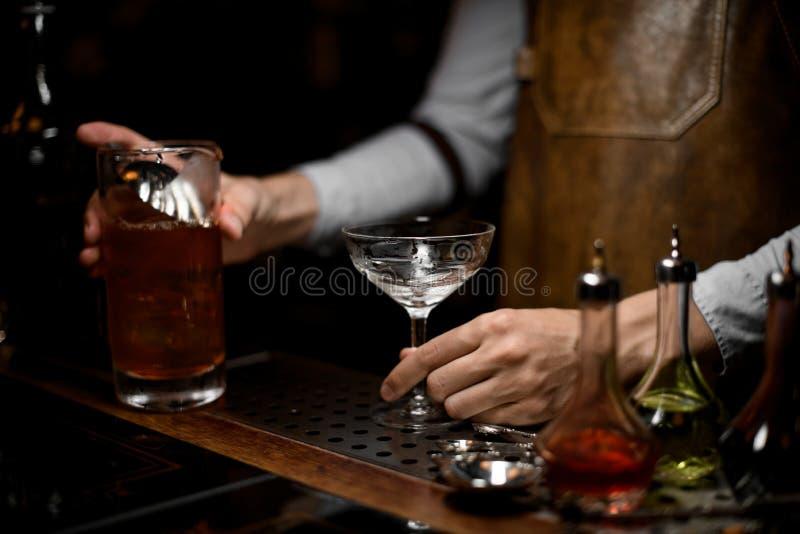 O barman derrama o cocktail do álcool com o filtro fotos de stock