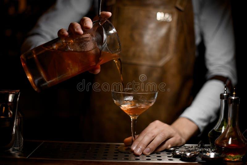 O barman derrama o cocktail do álcool com filtro fotografia de stock