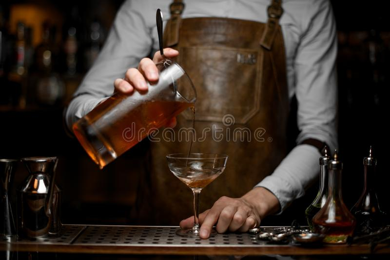 O barman derrama o cocktail do álcool de um filtro fotografia de stock royalty free