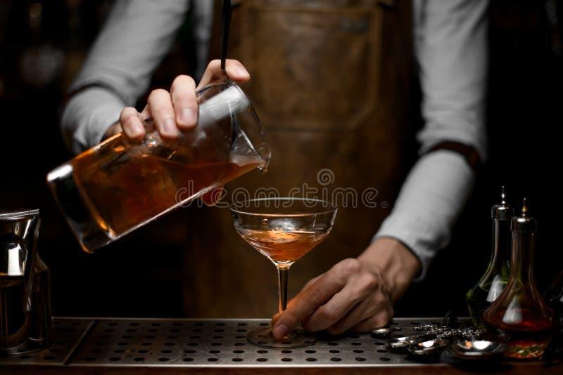 O barman derrama o cocktail do álcool do filtro fotos de stock