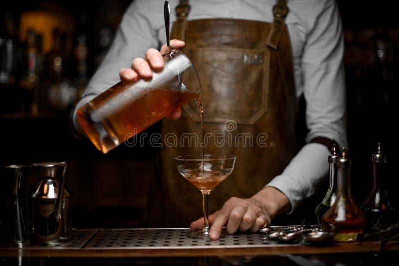 O barman derrama o cocktail do álcool do filtro fotografia de stock