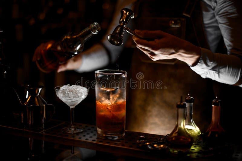 O barman derrama o cocktail do álcool usando o jigger com punho imagem de stock royalty free