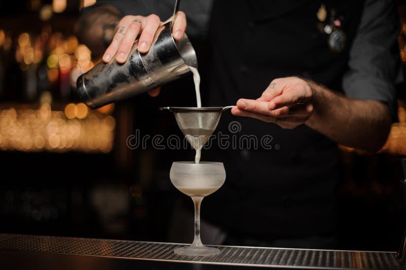 O barman derrama o cocktail que adiciona a mistura ácida no vidro fotos de stock royalty free