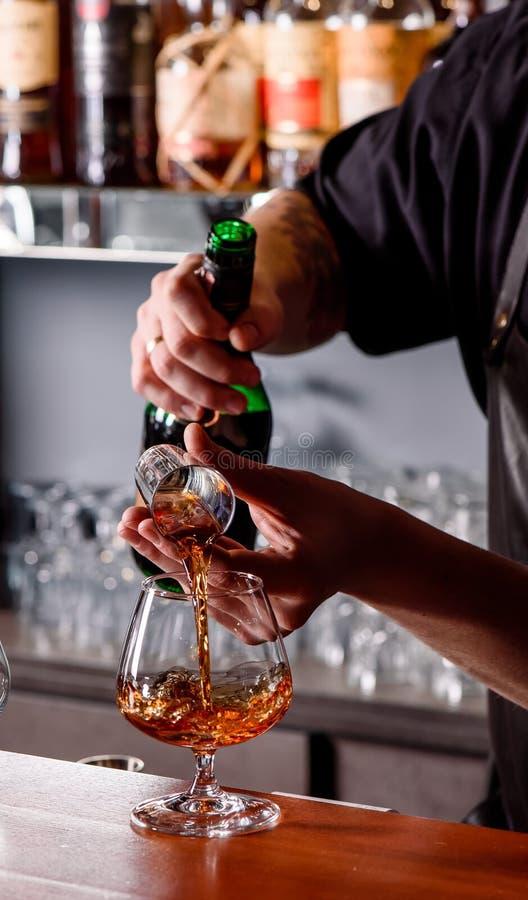 O barman derrama o conhaque em um copo de conhaque de vidro atrás de um contador de madeira da barra contra uma barra borrada imagem de stock royalty free