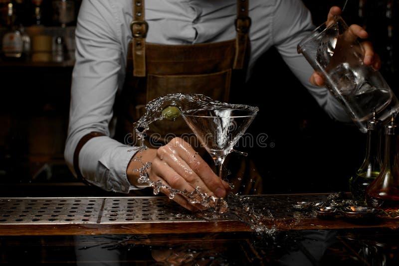 O barman derrama um cocktail de martini do frasco fotografia de stock