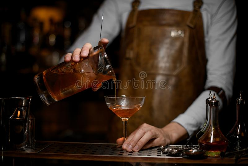 O barman derrama um cocktail do álcool com filtro fotografia de stock