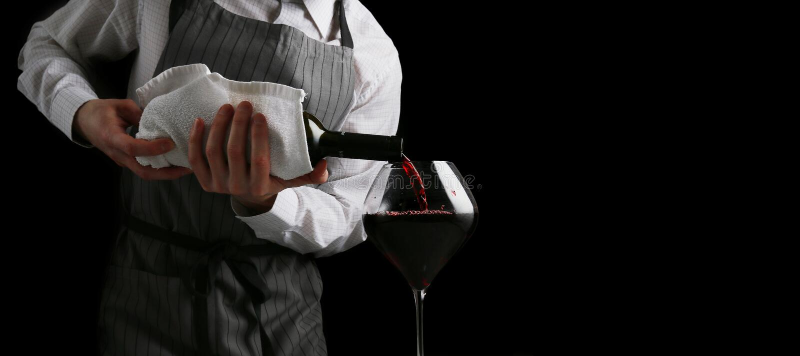 O barman derrama o vinho no baner de vidro no fundo escuro fotos de stock