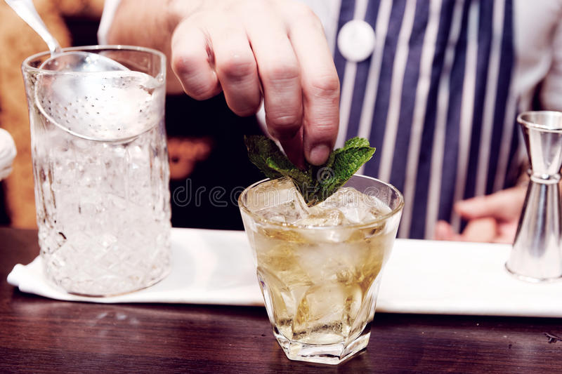 O barman está fazendo o cocktail no contador da barra, tonificado foto de stock
