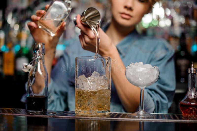 O barman fêmea que derrama ao copo de medição com gelo cuba uma bebida alcoólica do jigger de aço fotos de stock royalty free