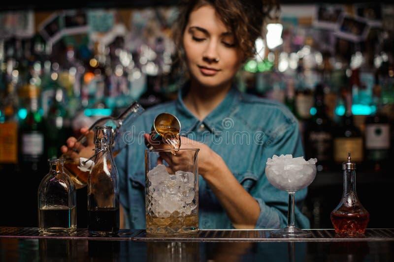 O barman fêmea que derrama ao copo de vidro da medição com gelo cuba uma bebida alcoólica do jigger fotos de stock royalty free