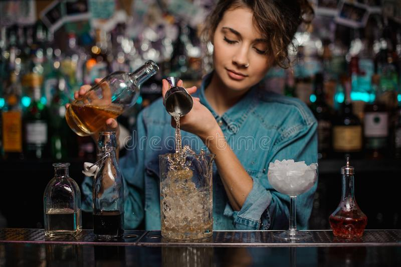 O barman fêmea que derrama ao copo de vidro da medição com gelo cuba uma bebida alcoólica do jigger de aço fotos de stock royalty free