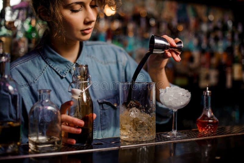 O barman fêmea que derrama ao copo de vidro da medição com gelo cuba uma bebida alcoólica marrom do jigger de aço imagem de stock royalty free
