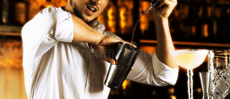 O barman incendiário derrama belamente o álcool do bott imagens de stock