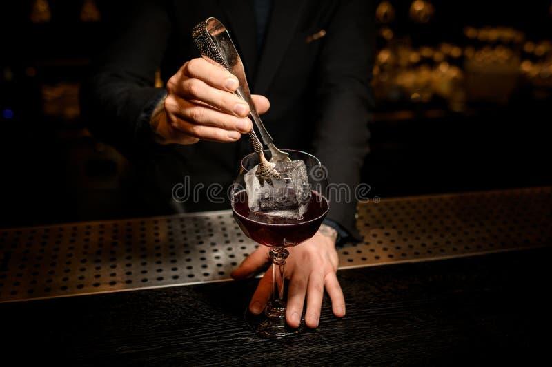 O barman põe o cubo de gelo grande em um cocktail com fórceps fotos de stock