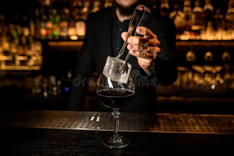 O barman põe o cubo de gelo grande em um cocktail foto de stock