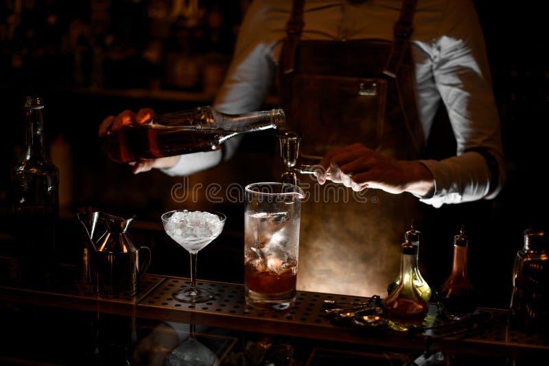 O barman prepara o cocktail do álcool usando o jigger com punho fotografia de stock royalty free