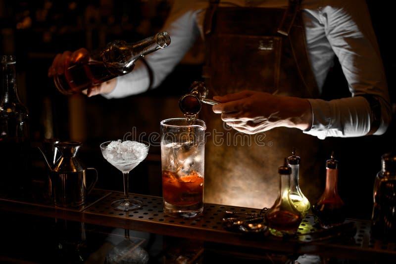 O barman prepara um cocktail do álcool usando o jigger fotografia de stock royalty free